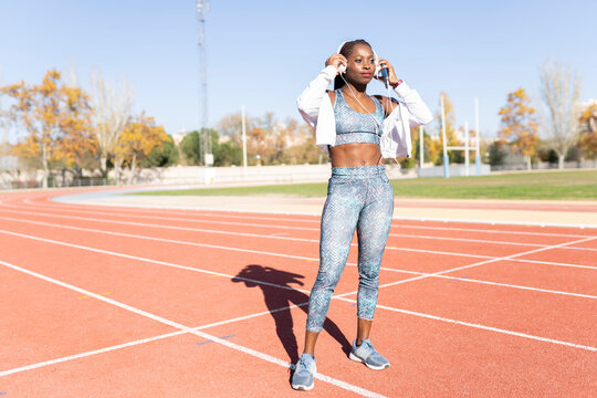 Female athlete wearing headphones while standing on sports track during sunny day