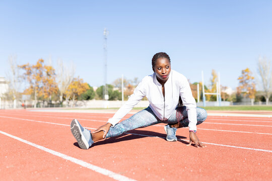 Young sportswoman looking away while doing warm up exercise on sports track against clear sky