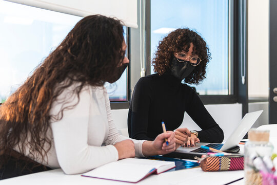 Female entrepreneurs working on laptop together in board room at work place