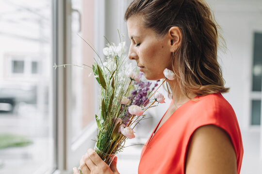 Woman smelling flowers at window