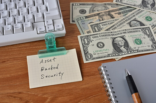 On the desk were bills, a keyboard, and memos with the word Asset Backed Security written on it.