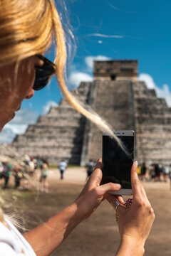 Mexico, Yucatan, Chichen Itza, Hands of female tourist taking smart phone photos of Temple Of Kukulcan