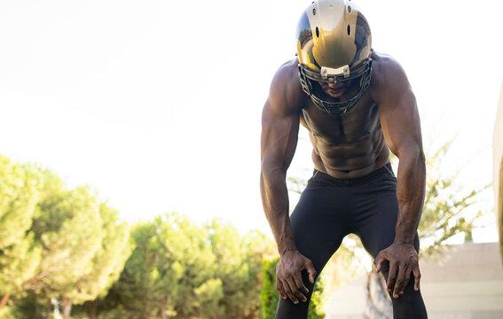 Tired male athlete wearing sports helmet in park