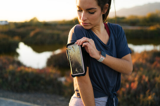 Young woman adjusting smart phone in arm band while standing against landscape