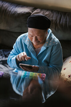 Smiling senior woman using smart phone at home