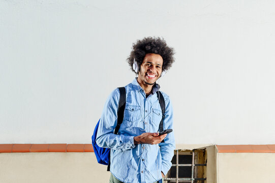 Smiling young man with smart phone standing against white wall