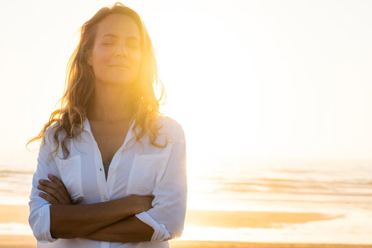 Woman standing with eyes crossed at beach during sunset
