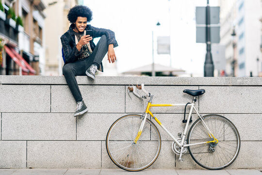 Young man with curly hair using smart phone while sitting on retaining wall