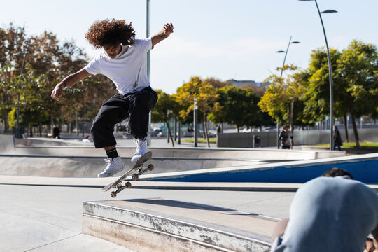 Young sportsman practicing while skateboarding at skateboard park