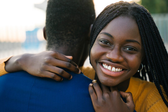 Happy teenage girl embracing boyfriend outdoors