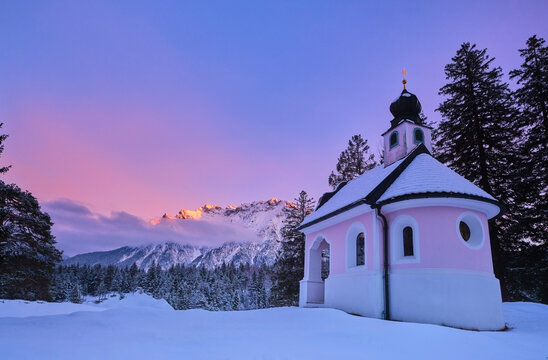 Chapel on snow covered land against sky during sunset