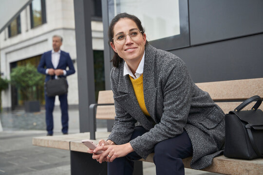 Smiling businesswoman sitting on bench waiting at bus stop while businessman standing in background