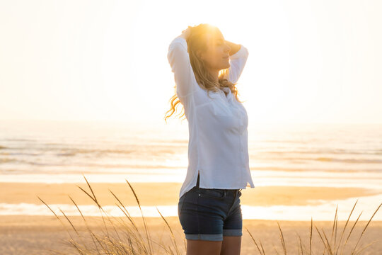 Carefree woman with hands behind head standing at beach