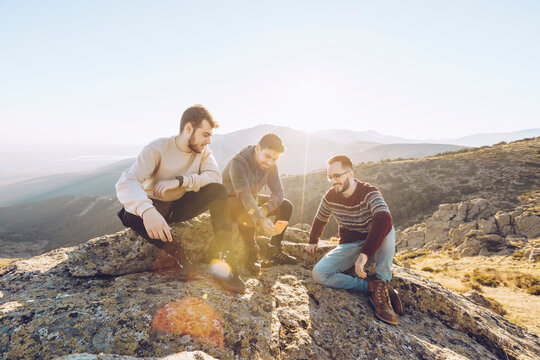 Male friends talking while sitting on mountain against clear sky during summer