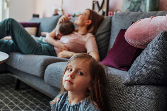 Mother with elder daughter while sister sitting below couch in living room