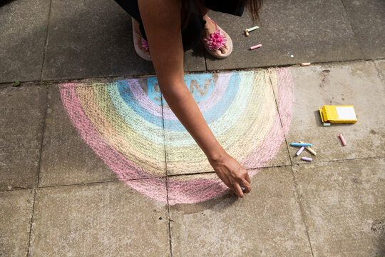 Arm of adult woman drawing crayon rainbow on pavement