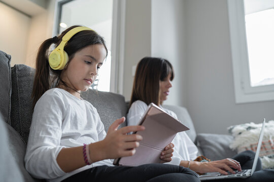 Mother working from home while her daughter plays with her tablet during their joint custody week, Spain