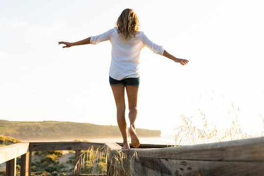 Mid adult woman balancing while walking on wood railing