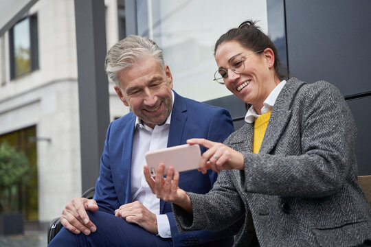 Cheerful businesswoman sharing smart phone with senior male colleague while waiting at bus stop