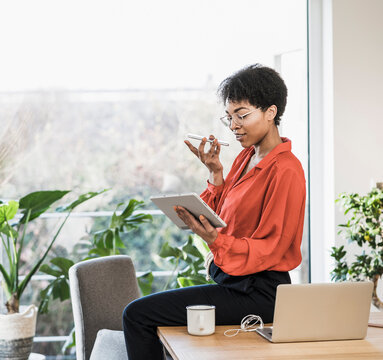 Woman using smart phone and digital tablet at table with laptop at home
