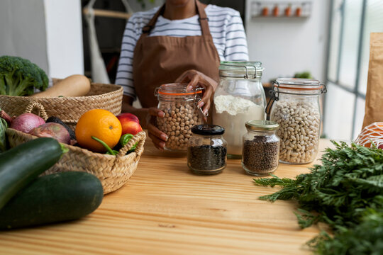 Woman with apron storing pulses in jars on table with fresh fruit and vegetables