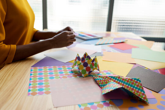 Origami artist sitting in studio folding colorful paper