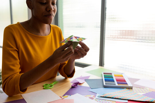 Origami artist sitting in studio working with colorful paper