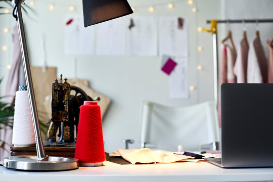 Thread spools and sewing machine with laptop on desk at design studio