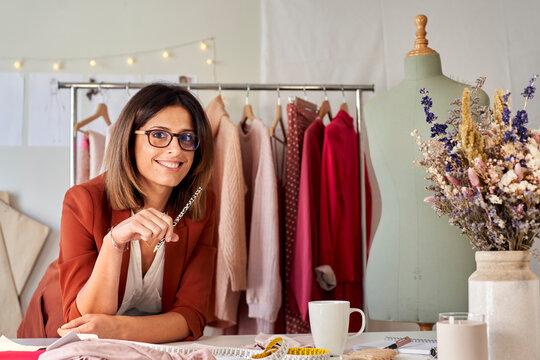 Happy beautiful female fashion designer leaning on desk at design studio