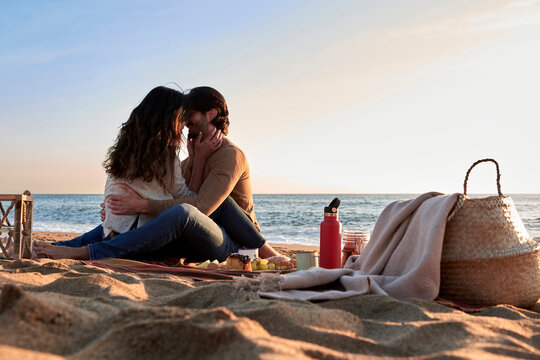 Girlfriend and boyfriend romancing while sitting face to face on beach