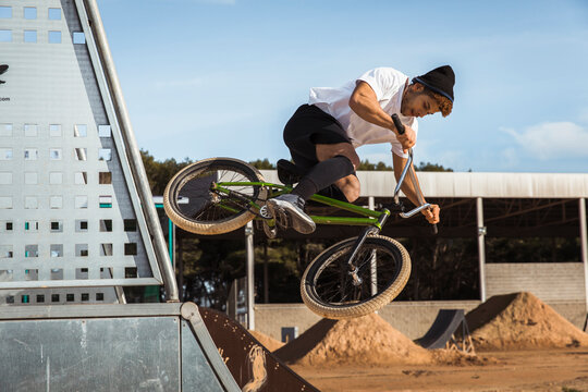 Young man jumping with bicycle at bike park on sunny day