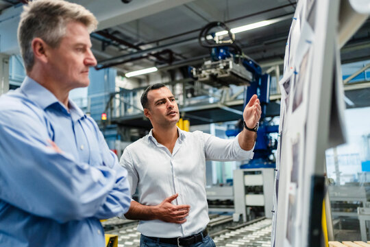 Mature male professional having meeting by whiteboard in factory