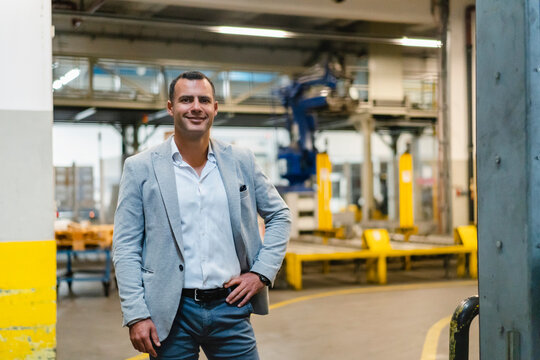 Smiling businessman with hand on hip standing in factory
