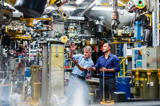 Mature male professionals discussing while surrounded by machines in industry