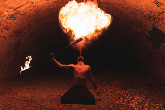 Male juggler performing with fire staff in dark tunnel