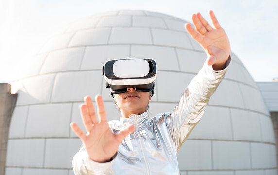Woman wearing protective suit gesturing while using virtual reality headset against igloo