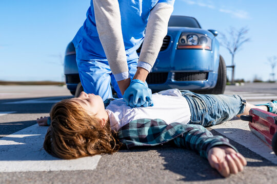 Rescue worker using giving CPR to victim lying on road after car accident