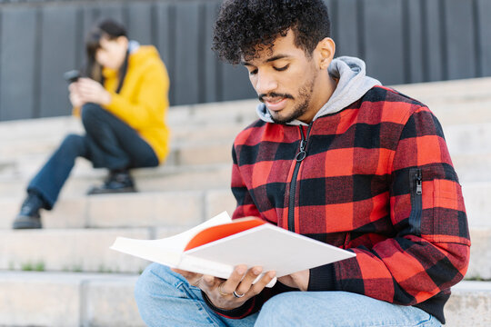 Young man wearing hooded shirt reading book while sitting by skateboard on steps