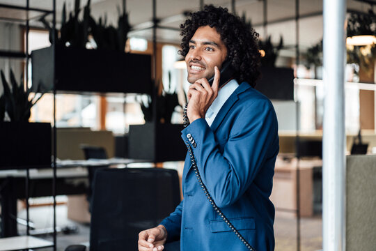 Smiling male professional talking on landline phone in office