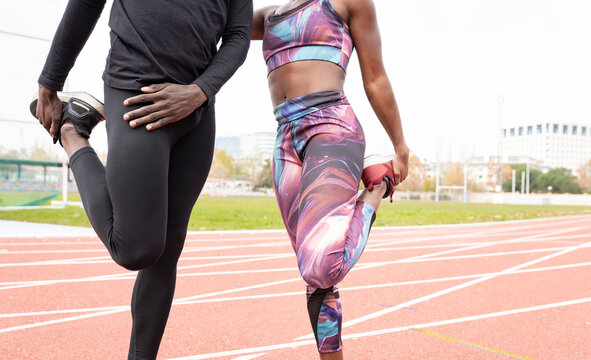 Male and female sportsperson stretching while standing on running track
