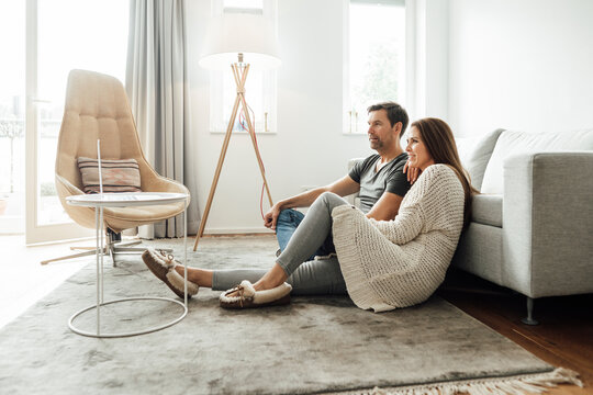 Mature couple watching movie on laptop while sitting in apartment