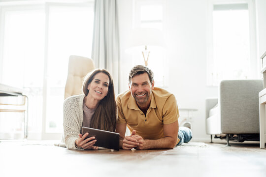 Smiling mature man and woman with digital tablet lying on floor in apartment