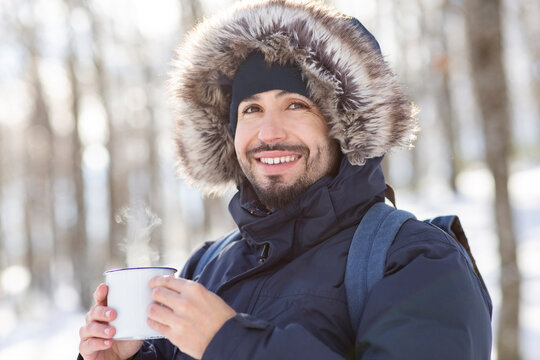 Happy man day dreaming while holding coffee cup