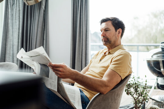 Mature man reading newspaper in living room at home
