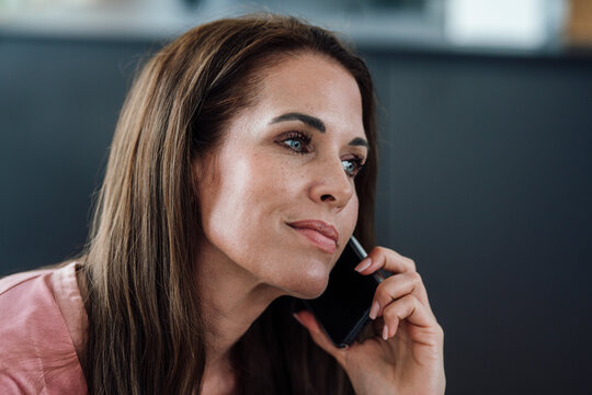 Smiling mature woman with gray eyes on phone call in apartment
