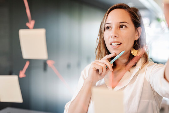 Close-up of businesswoman planning over adhesive notes stuck on glass wall in office