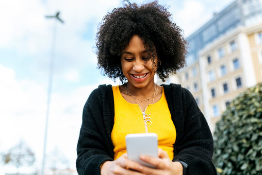 Smiling beautiful woman using mobile phone while sitting against sky
