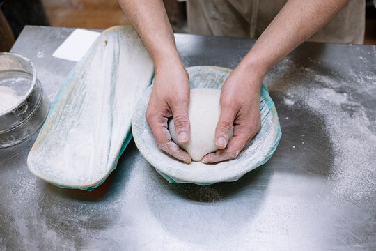 Male baker keeping flour dough in container in kitchen at bakery
