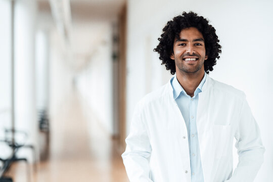 Smiling young male doctor standing at hospital corridor