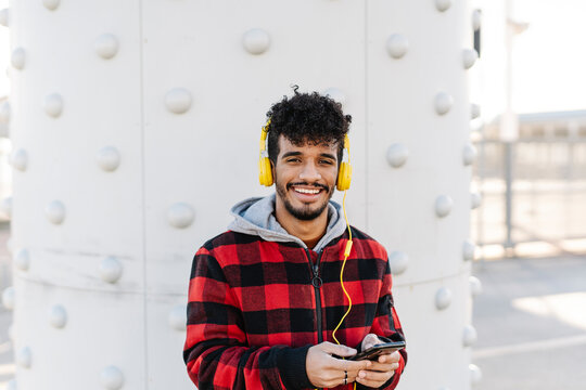 Man wearing hooded shirt listening music through headphones while standing with mobile phone against wall
